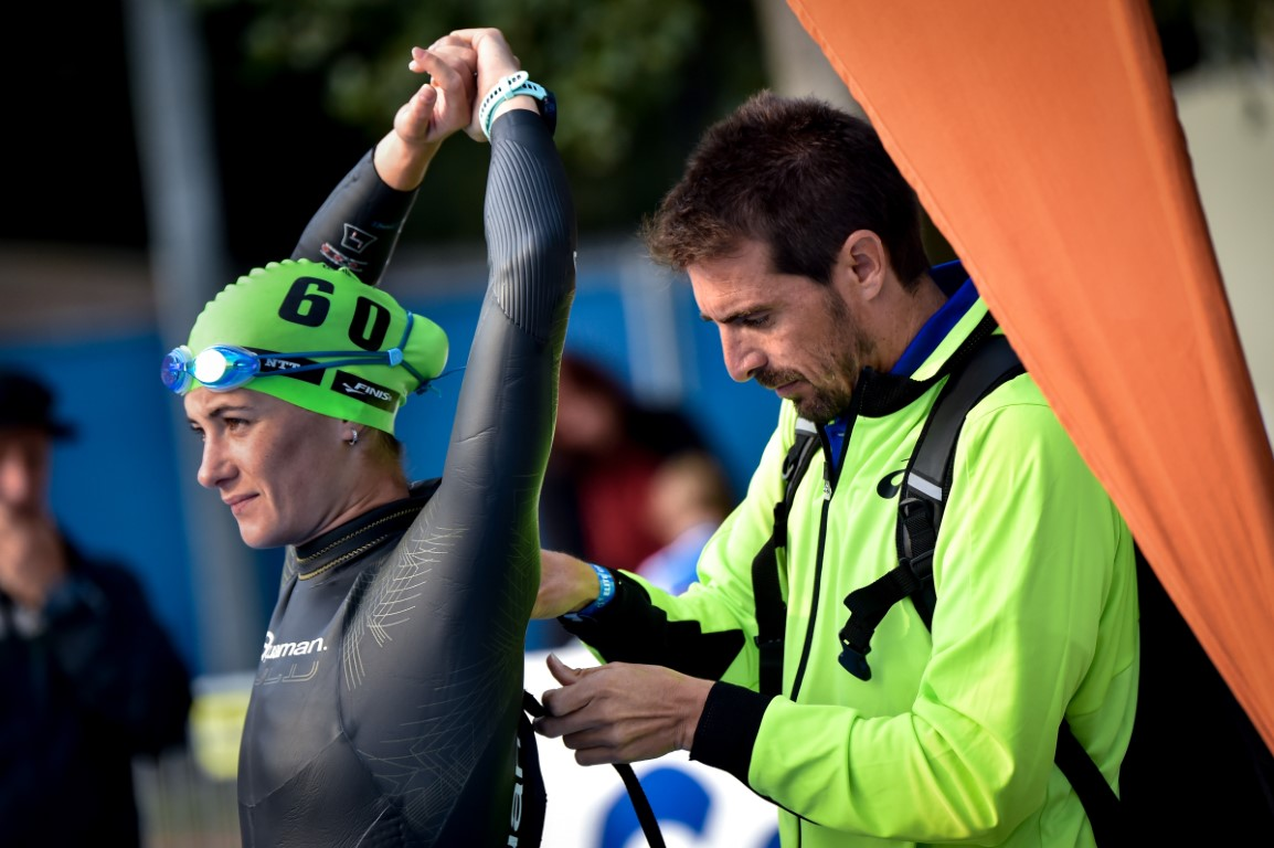 Coach helping a triathlete do up their swimsuit