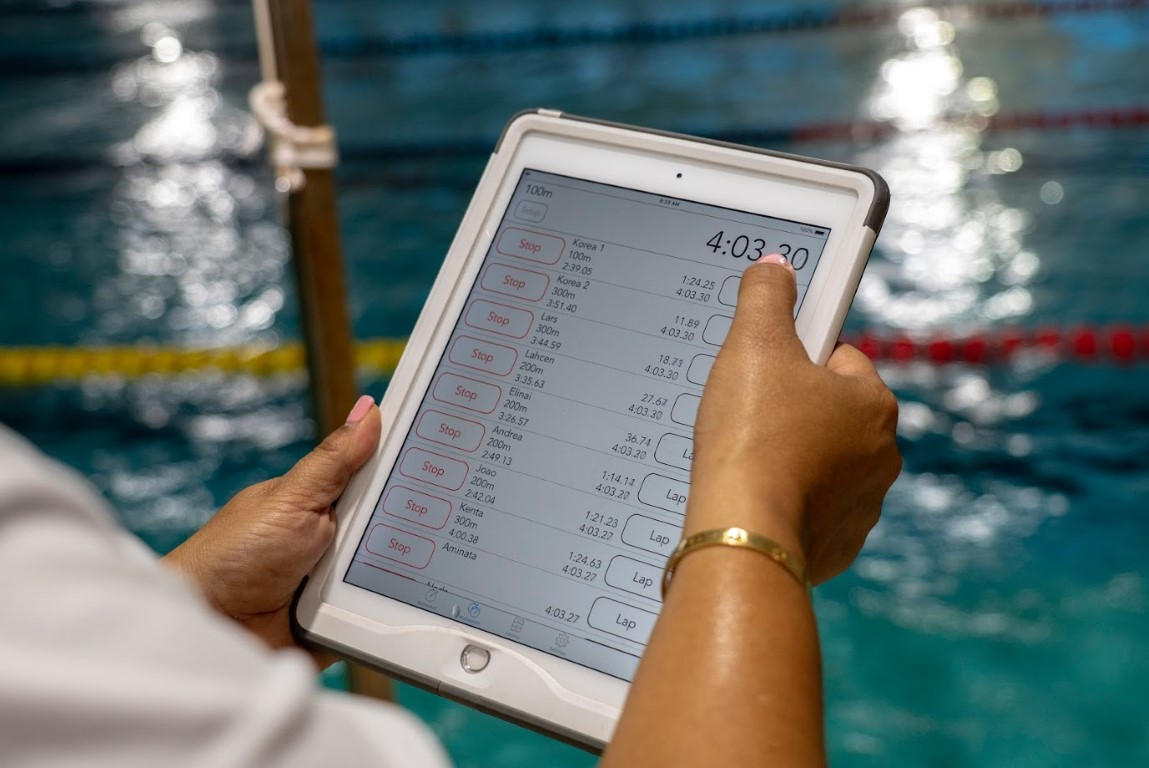 coach using a tablet device to record times at the pool